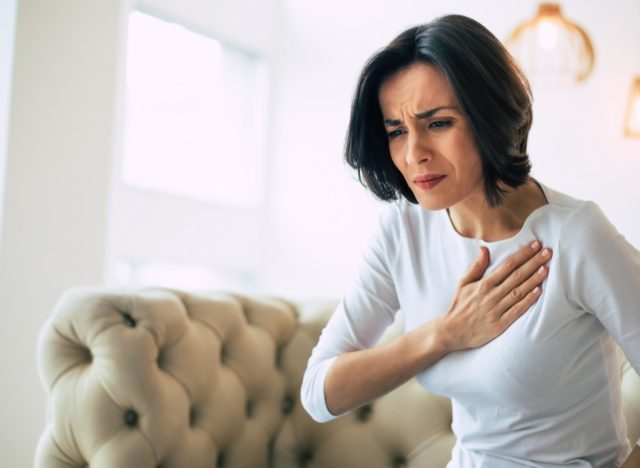 woman who is suffering from a chest pain and touching her heart area