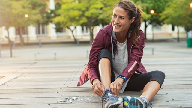Mature fitness woman tie shoelaces on road