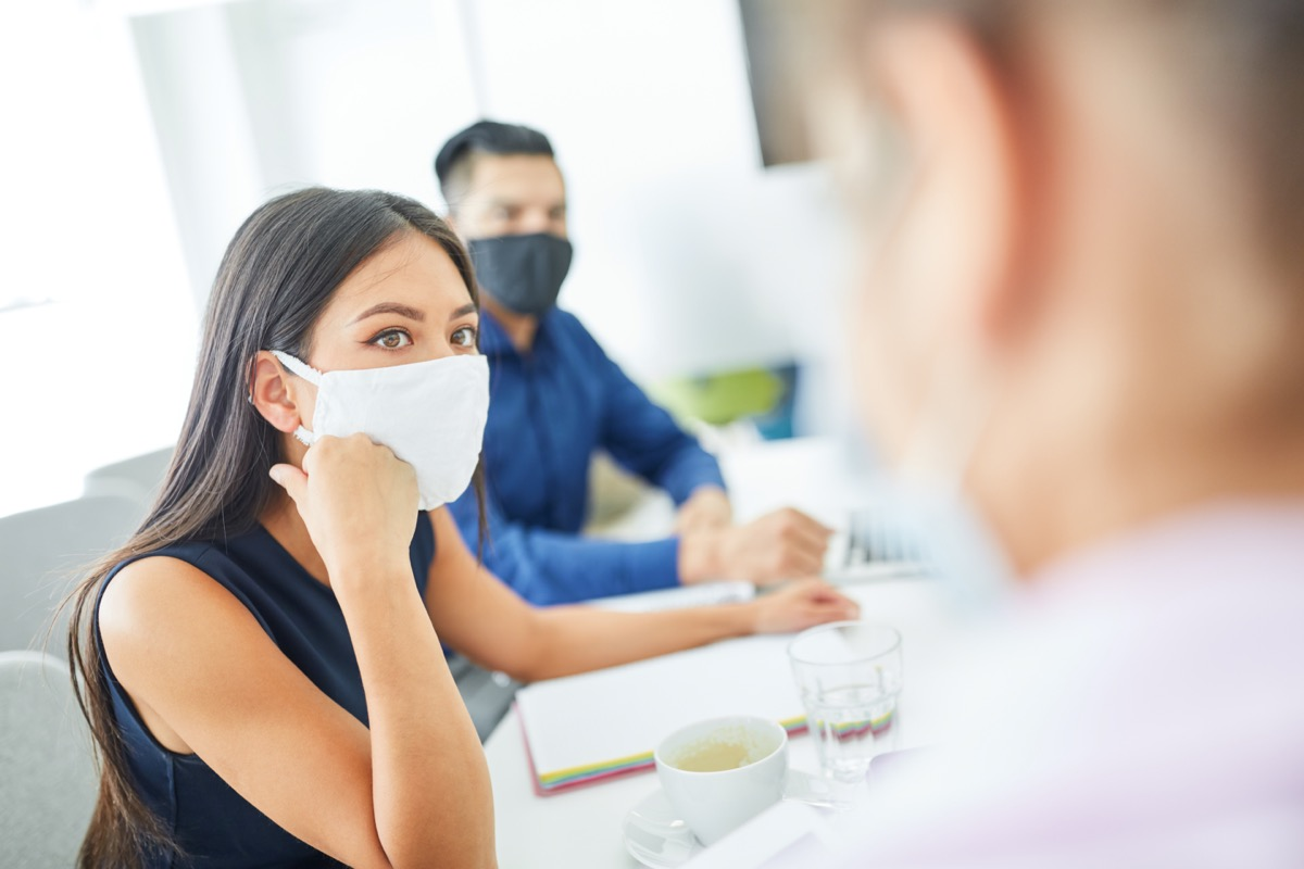 Business woman with face mask because of Covid-19 and corona virus in a meeting or a meeting