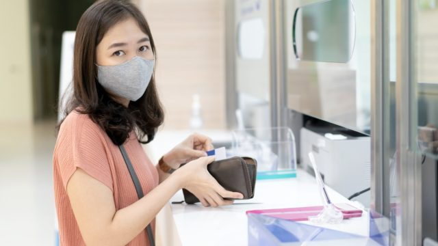 woman with hygiene face mask standing in front of cashier counter in hospital