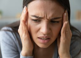 Woman touches temples with hands suffers from throbbing severe headache