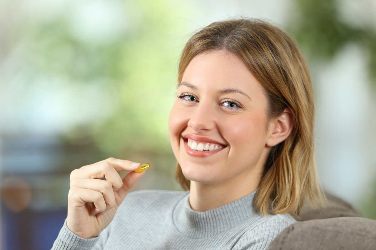 woman holding a vitamin pill