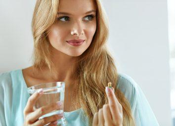 Woman holding pill