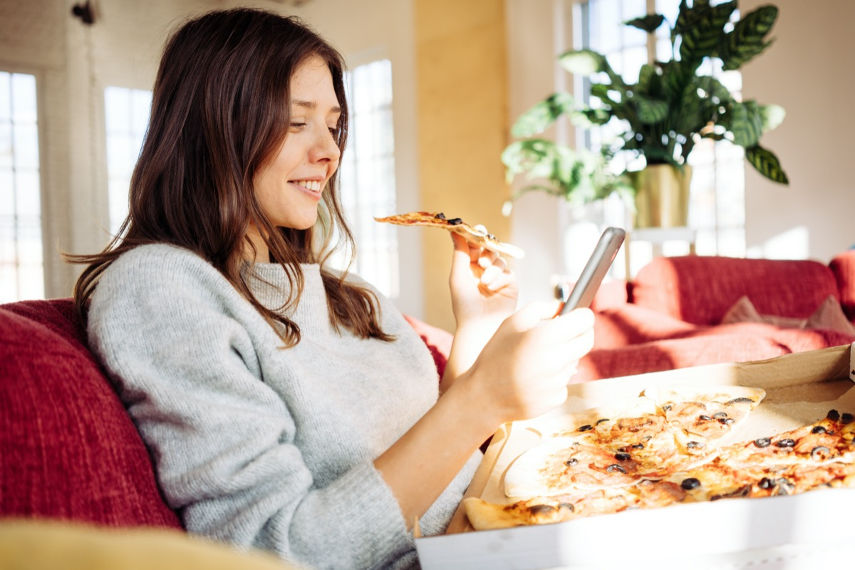 Woman eating pizza at home and taking photo of her food