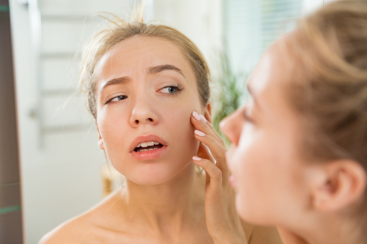 woman touching skin in bathroom
