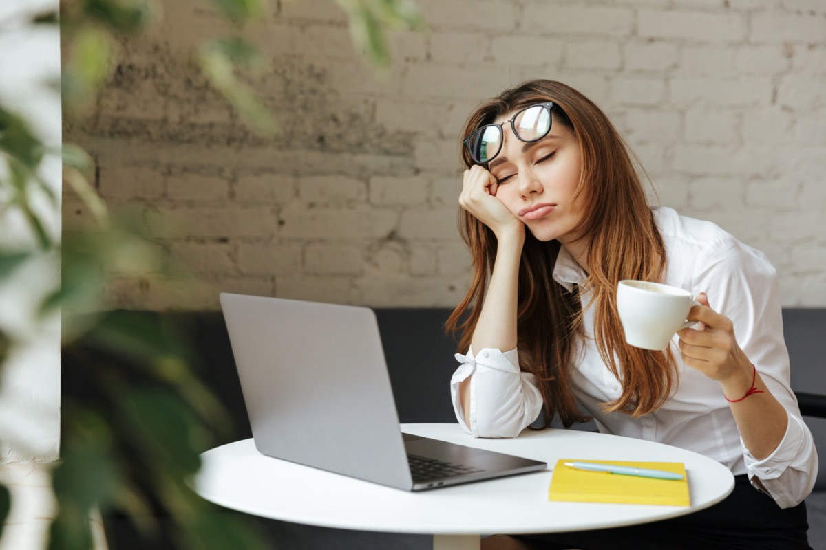 womany sleepy leaning on coffee table