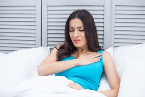 Woman lying in bed at home holding a hand to her chest by a sharp pain