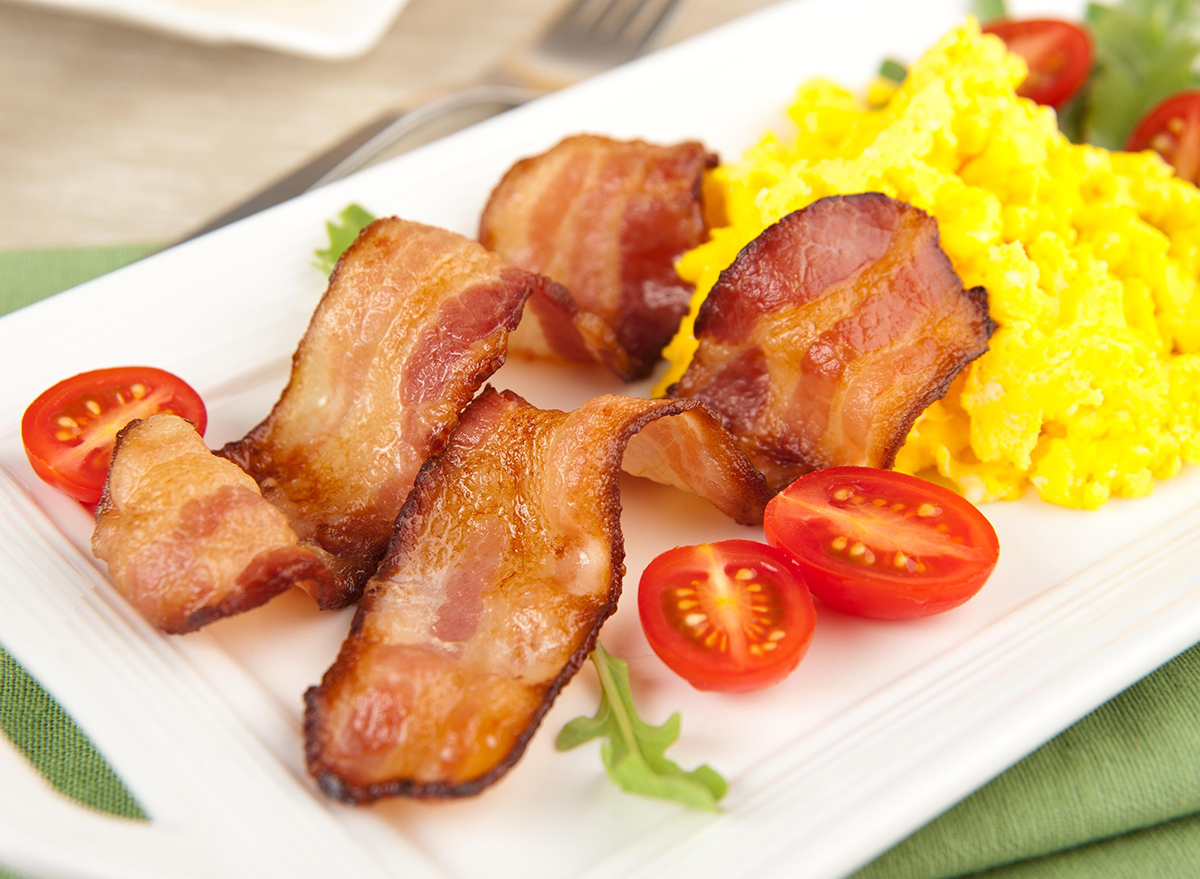 bacon strips with eggs tomatoes and arugula