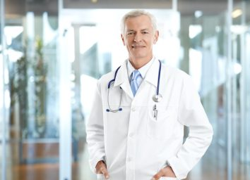 senior male doctor wearing lab coat and standing at private clinic