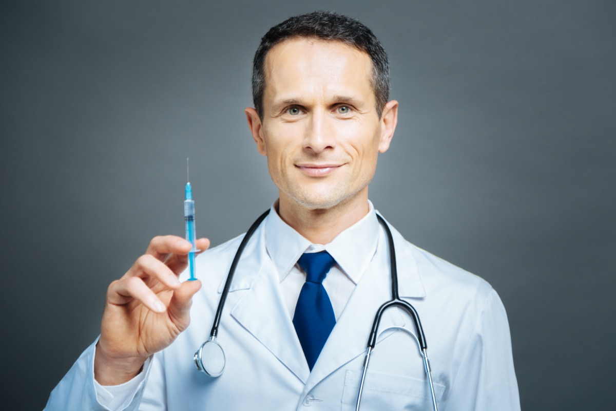 Cheerful practitioner holding syringe and smiling