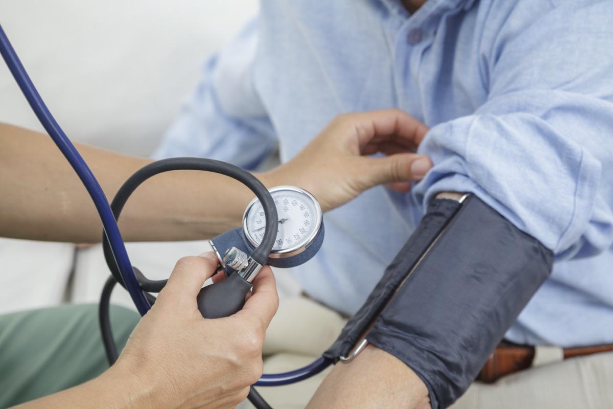 Nurse taking the blood pressure of elderly man