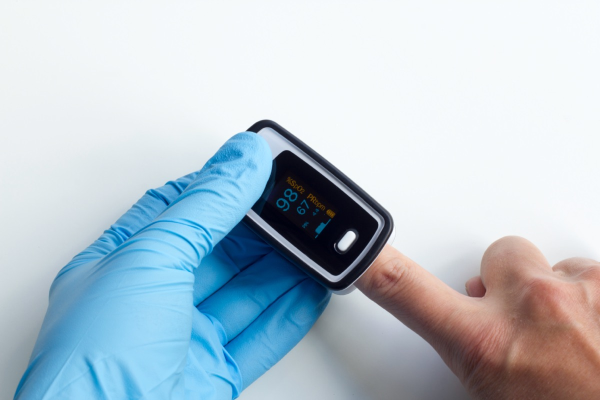 Doctor wearing blue nitrile exam gloves performs a test using a fingertip pulse oximeter to check the patient's oxygen saturation level and pulse rate