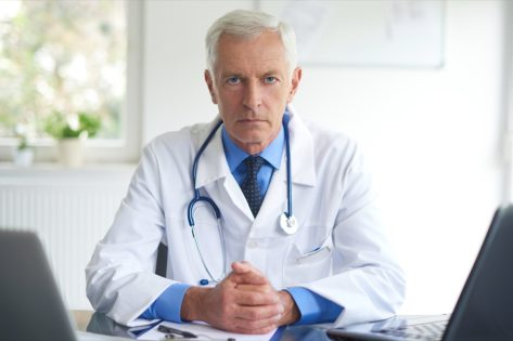 Portrait of senior male doctor sitting at doctor's office and working on laptop.
