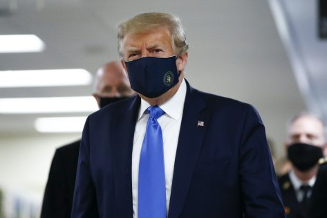 President Donald Trump wears a mask as he walks down the hallway during his visit to Walter Reed National Military Medical Center in Bethesda