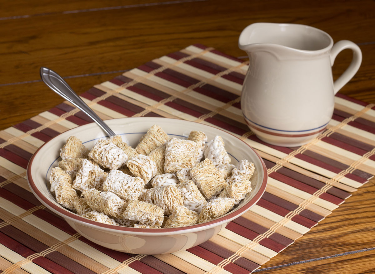 bowl of mini wheats cereal with pitcher of milk