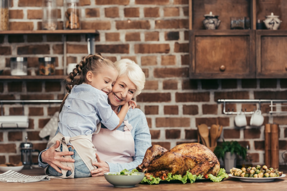 grandmother and granddaughter embracing on kitchen and looking at freshly prepared turkey for thanksgiving dinner