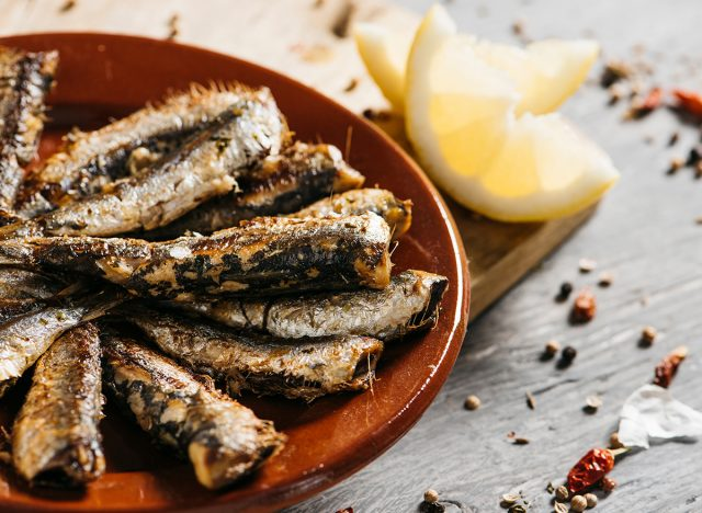 grilled sardines on plate with lemon wedge