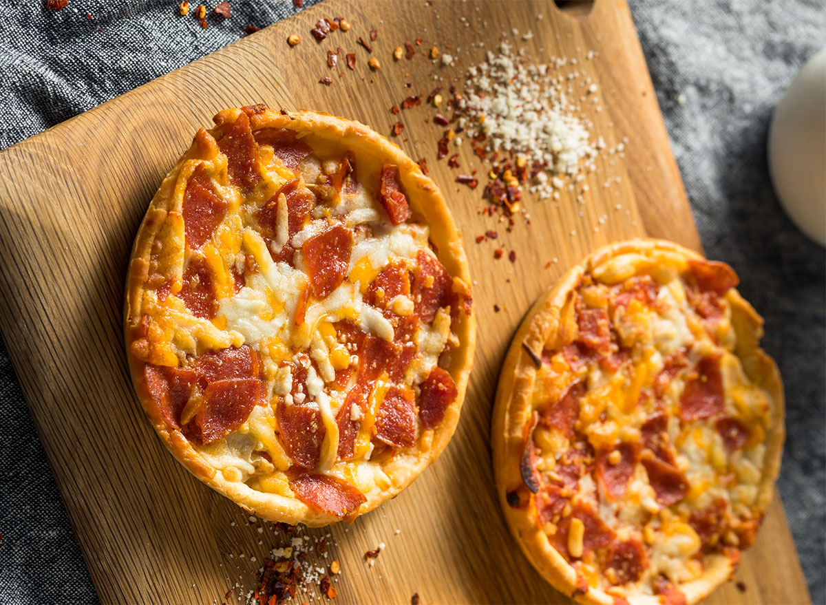 two individual frozen pizzas on wooden board