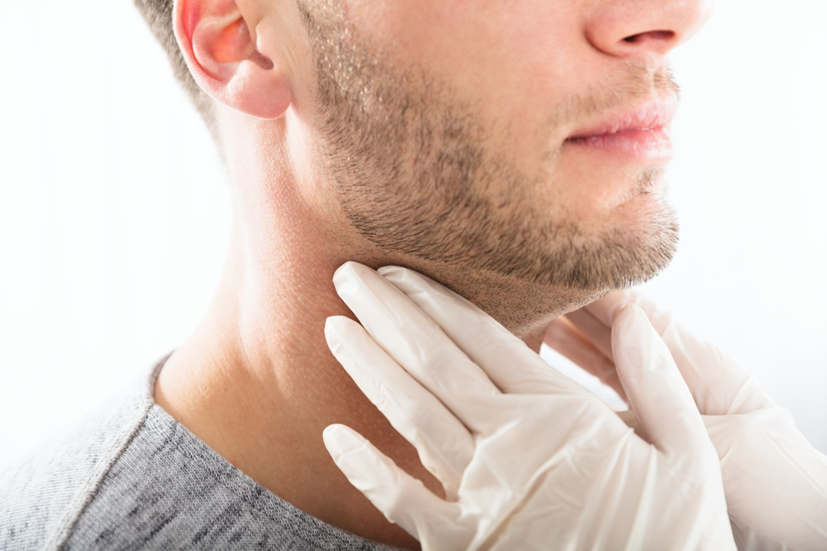 Doctor Performing Physical Exam Palpation Of The Thyroid Gland