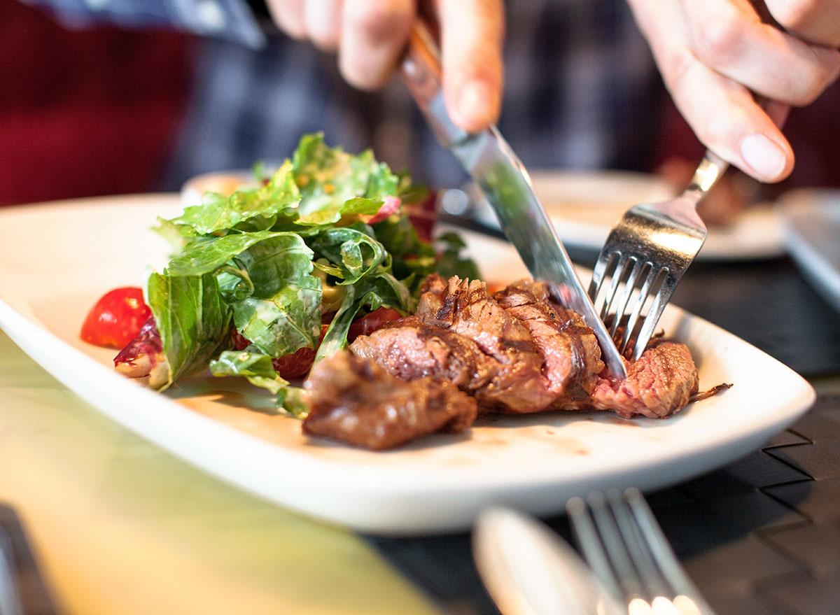 man eating steak