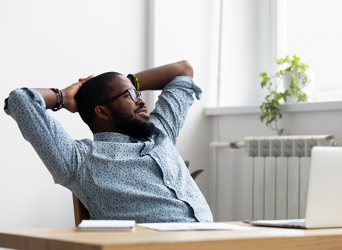 man sitting at desk looking out window