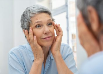 woman checking her face skin and looking for blemishes