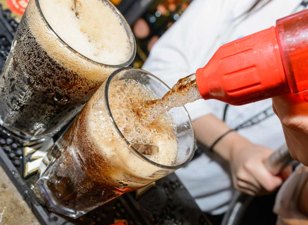 pour soda out of a tap at a bar into an alcoholic cocktail drink