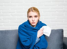 Woman Feeling Sick or Sad Wrapped in Cozy Blue Blanket
