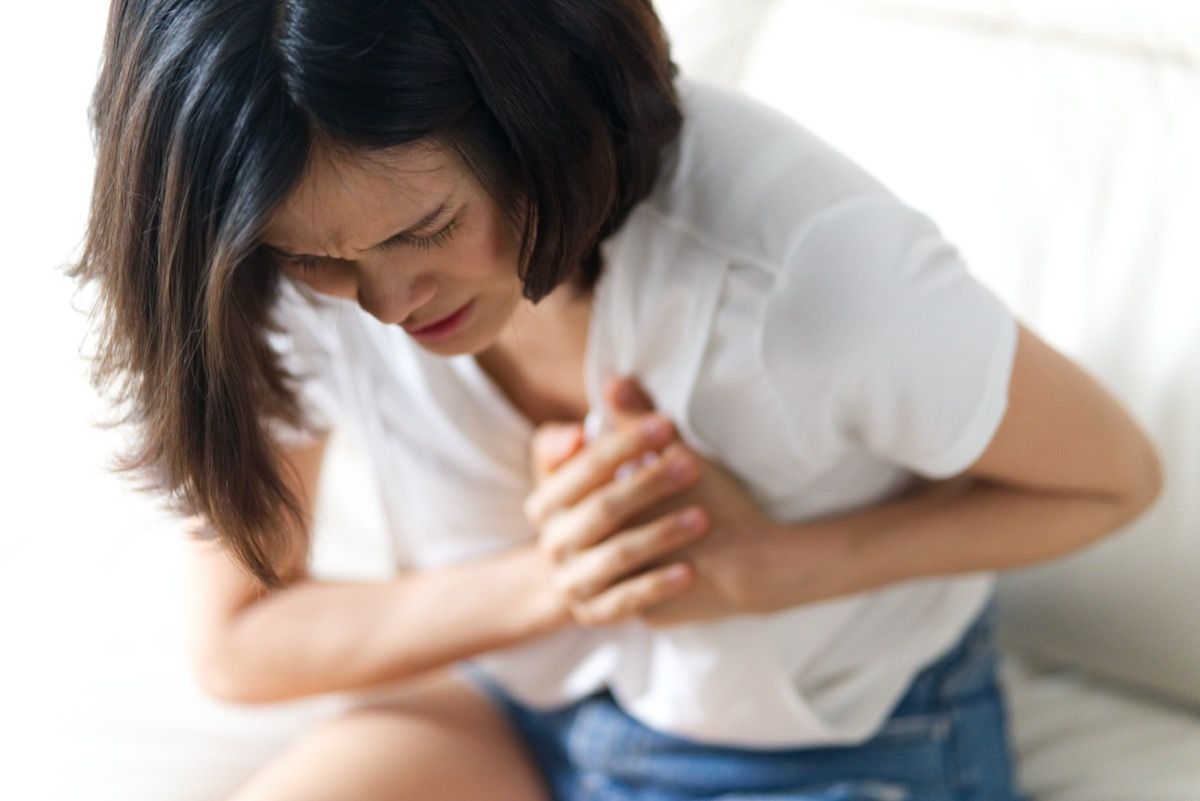 Woman having bad ache and pain heart attack health problem.