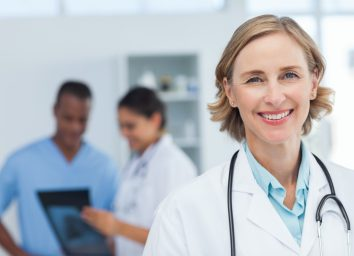 Woman doctor smiling and looking to the camera while a medical team is working.