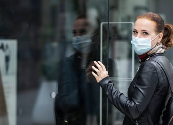 Woman at the entrance to a closed clothing store.