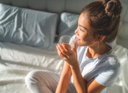 Woman drinking tea and water in bed in the morning