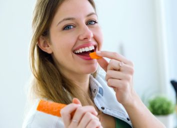 Woman eating carrot in the kitchen.