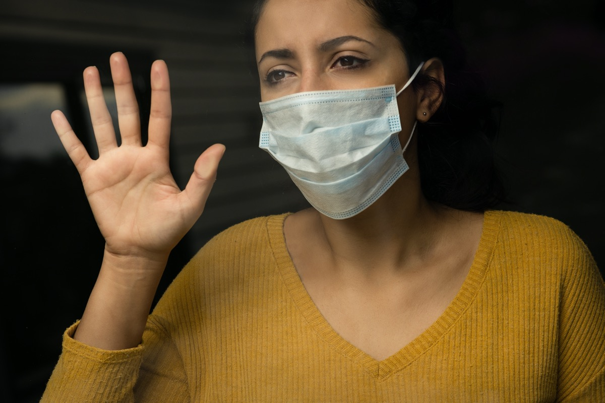 sad woman wearing a face mask looking through the window