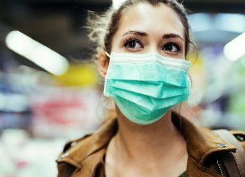 Woman wearing protective mask on her face while being in the store during coronavirus epidemic