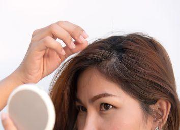 woman looking in mirror finding gray hair