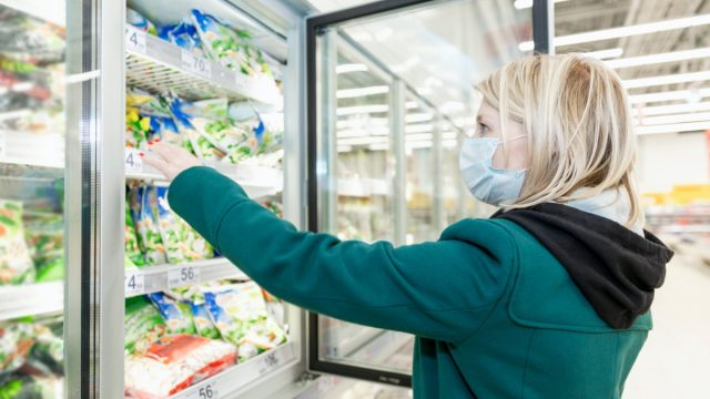 woman in a medical mask is shopping at a supermarket in the frozen food department