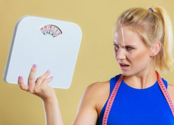 woman frustrated and angry about her scale and weight loss