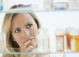 A woman is looking through her medicine cabinet.