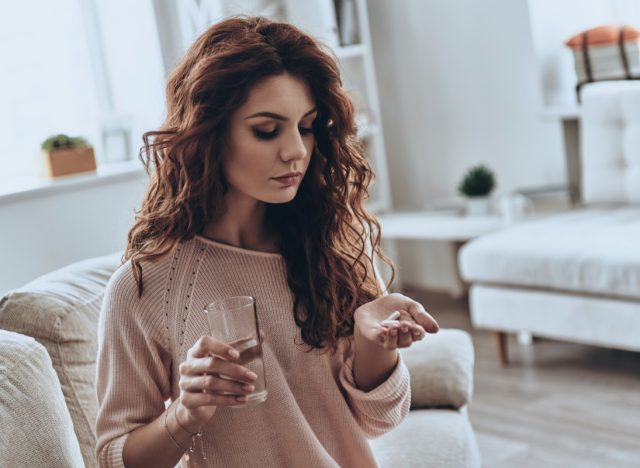 Woman holding pills on her hand.