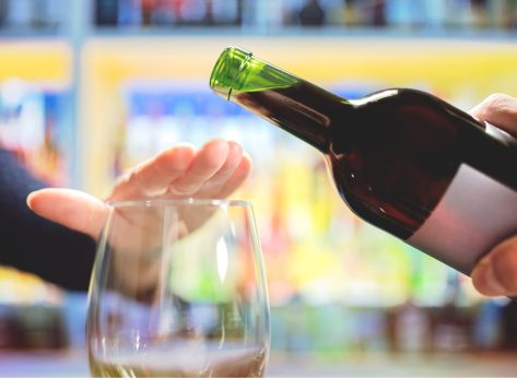 woman refusing or saying no to being poured a glass of wine alcohol