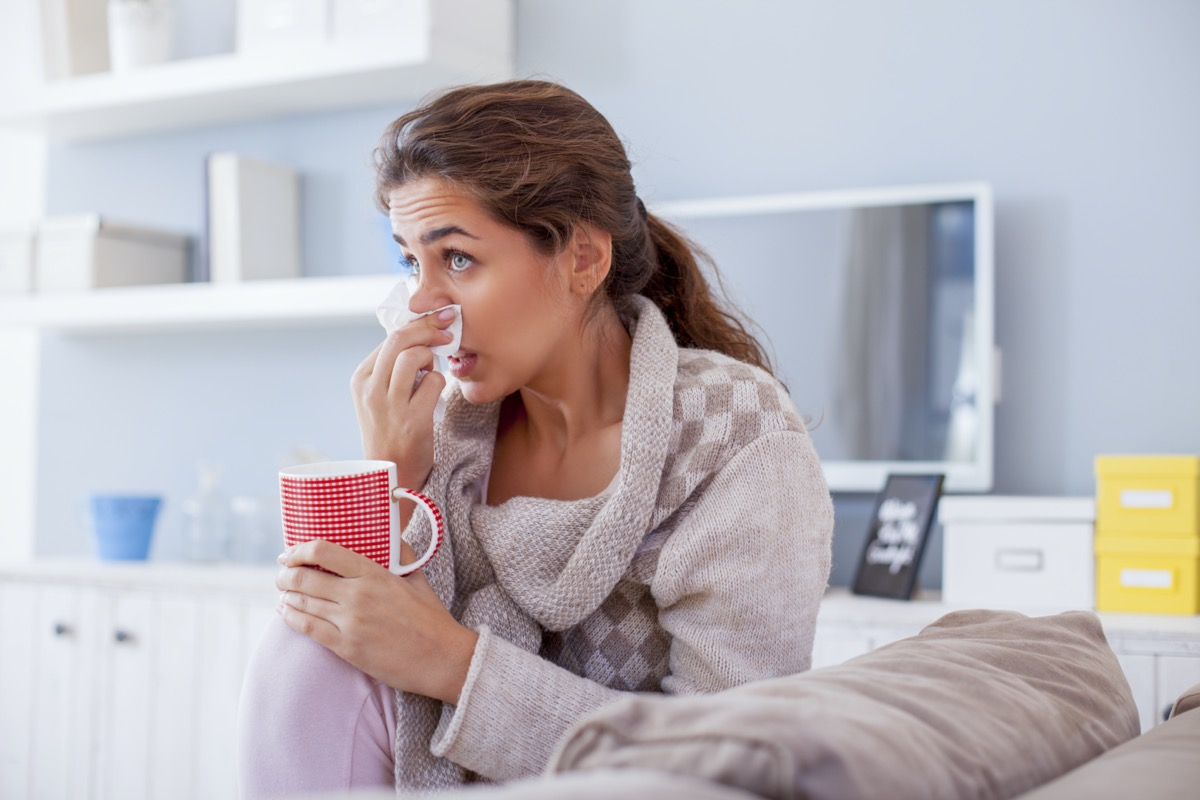 Sick woman blowing nose on her sofa.