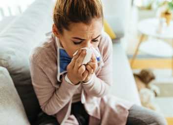 Young woman feeling sick and sneezing in a tissue at home.