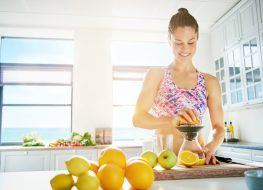 Fit smiling young woman preparing healthy fruit juice