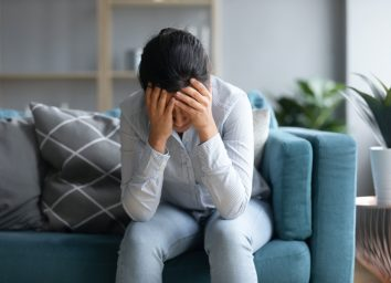 depressed Indian woman holding head in hands, sitting alone on couch at home