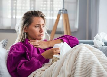 Woman experiencing first Covid-19 symptoms throat pain breathing problems on sofa