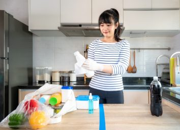 woman laying out groceries on a divided table and wiping down yogurt or milk containers bottle with disinfectant take to eliminate the chances of contamination COVID-19.