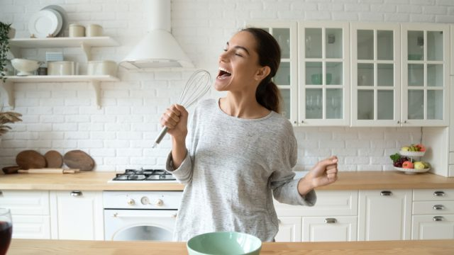 Happy woman singing in her kitchen