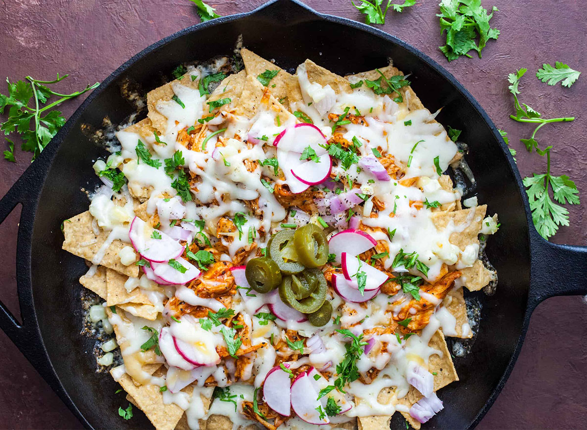 pan of nachos topped with cheese and radishes in a skillet