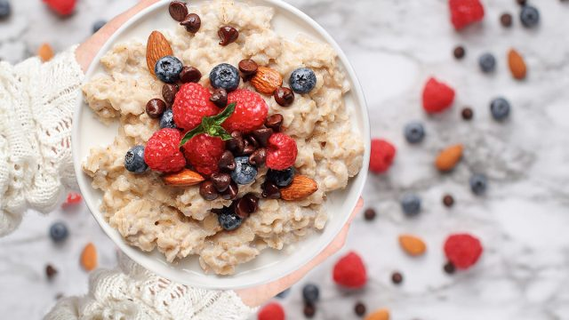 bowl of oatmeal with berries nuts and chocolate